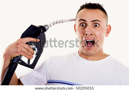 Stock image of man shouting and pointing a fuel pump nozzle at his head - stock photo