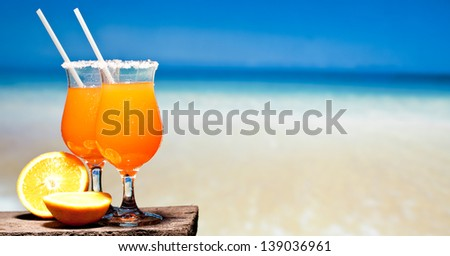 Stock image of Tequila Sunrise cocktail on wooden planks in front of a blue swimming pool or the ocean - stock photo