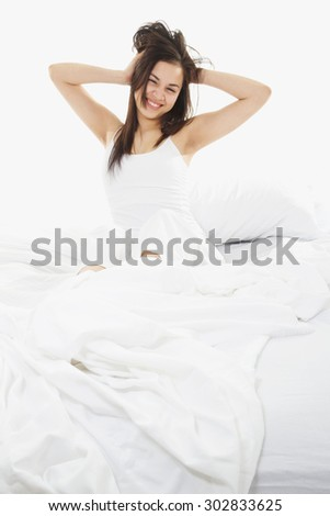 Stock image of woman in bed, white bedding - stock photo