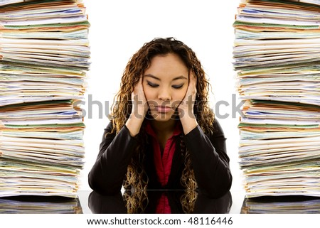 Stock image of woman sitting at desk with a pile of paperwork on each side - stock photo