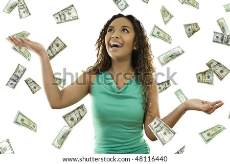 Stock image of woman standing with open arms amidst falling money - stock photo