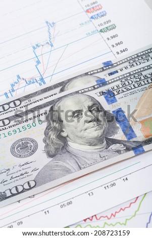 Stock market chart and 100 USA dollars bills - studio shot - stock photo