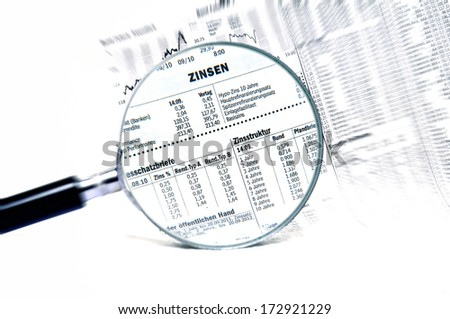 Stock market charts behind a magnifying glass - stock photo