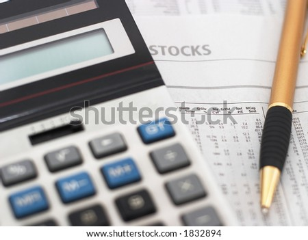 Stock market table analysis, calculator and pen indicates research and analysis, horizontal orientation, shallow depth of field, focus on text - stock photo