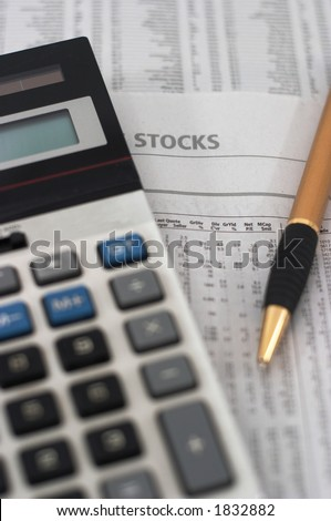 Stock market table analysis, calculator and pen indicates research and analysis, vertical orientation, shallow depth of field, focus on text. - stock photo