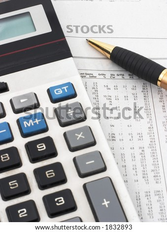 Stock market table analysis, calculator and pen indicates research and analysis, vertical orientation, pen pointing to word 'stocks' - stock photo