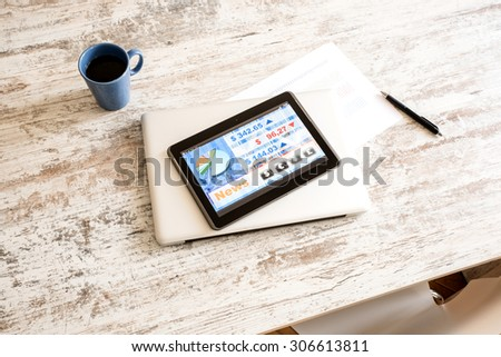 Stock market trading and research software on a Tablet PC on a office Desktop with a Laptop computer.  - stock photo