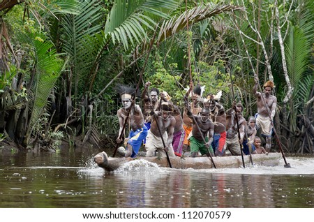 Stock Photo: INDONESIA, IRIAN JAYA, ASMAT PROVINCE, JOW VILLAGE - JUNE 28: Asmat men paddling in their dugout canoe. Canoe war ceremony of Asmat people. New Guinea Island, Indonesia. June 28 2012 - stock photo