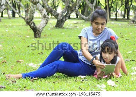 Stock Photo - Mother and young daughter using a digital tablet on the lawn - stock photo