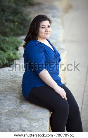 Stock photo of a casually dressed woman sitting in an outdoor urban environment.