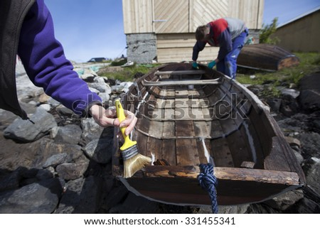 Stock photo of a hand holding paint brush in the process of applying oil on old wooden boat, to protect and preserve the wood - stock photo
