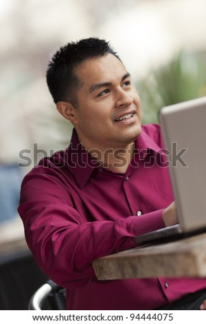 Stock photo of a happy Hispanic businessman looking down at his laptop computer while telecommuting at an internet cafe. - stock photo