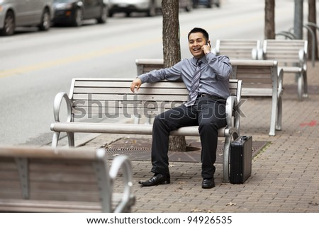 Stock photo of a Hispanic businessman laughs while sitting on a city bench and chatting on a cell phone with a happy expression. - stock photo