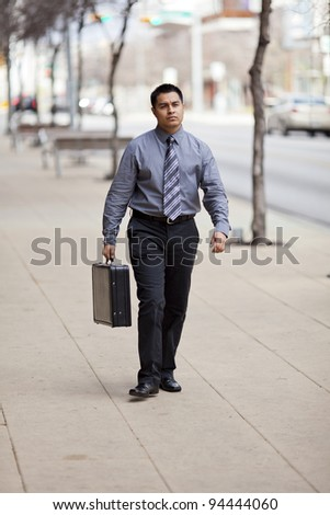 Stock photo of a Hispanic businessman walking in a downtown business district carrying a briefcase.