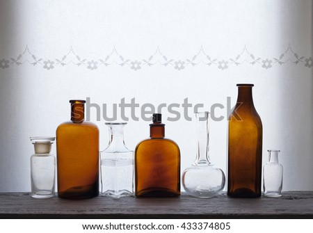Stock photo of a row of old empty brown and transparent glass bottles at windowsill against daylight - stock photo