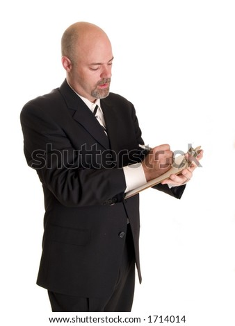 Stock photo of a well dressed businessman making notes on a clipboard. - stock photo