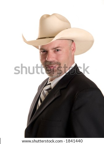 Stock photo of a well dressed businessman wearing a cowboy hat smiling at the camera, isolated on white. - stock photo