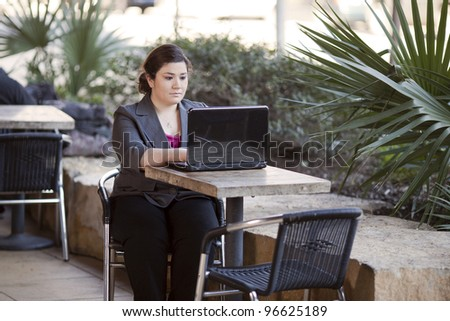 Stock photo of a well dressed businesswoman looking down at a laptop while telecommuting from an internet cafe.