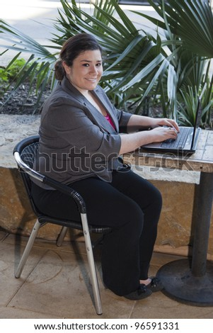 Stock photo of a well dressed businesswoman looking up at the camera and smiling as she works on a laptop while telecommuting from an internet cafe.