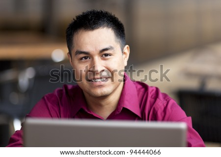 Stock photo of a well dressed Hispanic businessman looking up from a laptop while telecommuting from an internet cafe. - stock photo