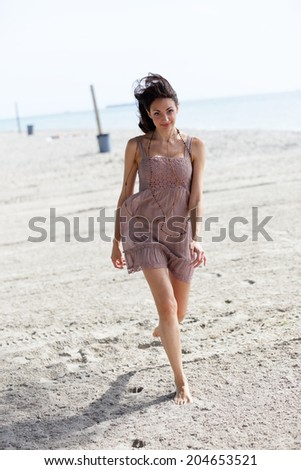 Stock photo of a woman running on the sand barefoot - stock photo