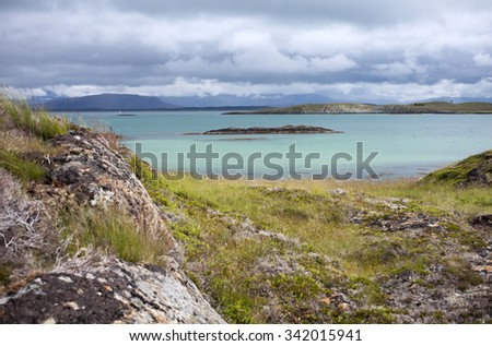 Stock photo of beautiful Norwegian landscape at sunny day at Helgeland archipelago, with clouds filling the sky at distance.   View at sea over rocks. Photographed at Skarvoya, Helgeland, Norway.  - stock photo