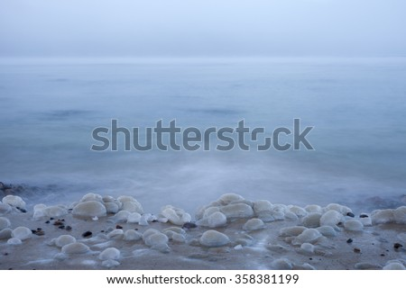 Stock photo of ice-covered small stones at beach at winter. Dreamy background because of evaporation and slow shutter speed.