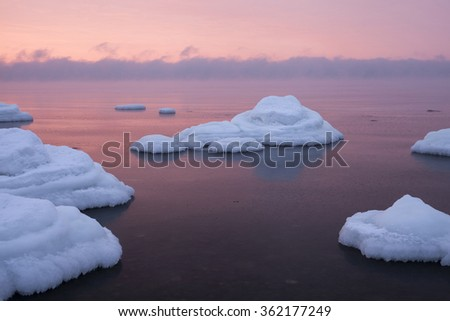 Stock photo of ice-covered stones looking like rounded white cakes in still sea at sunset at winter. Photographed at North coast of Estonia, Baltic sea.
