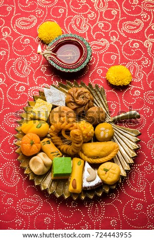 stock photo of Indian sweet or mithai and oil lamps or diya with flowers on decorative or colourful background, selective focus