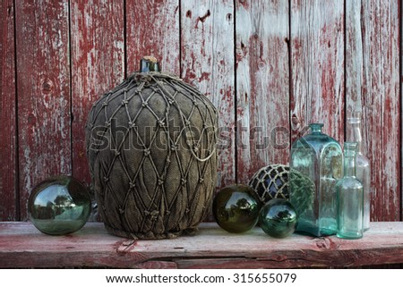 Stock photo of large antique glass wine bottle wrapped in textile, old glass bottles and buoys at weathered red plank wall. Photographed at Blomsoya, Nordland, Norway. - stock photo