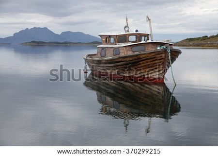 Stock photo of old wooden fishing boat at Norwegian coast, mountain at background.