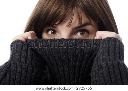 Stock photo of pretty young woman holding sweater collar, close-up