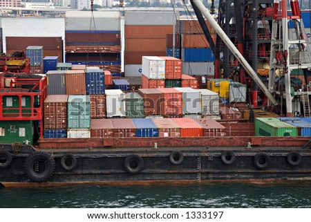Stock photo of shipping containers on board lighters at a container terminal on Victoria Harbour Hong Kong, stacked containers in background.
