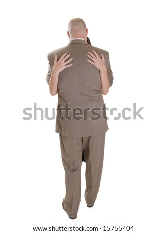 Stock photo of the back side of a well dressed businessman being embraced by a woman. - stock photo