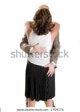 Stock photo of the back side of a well dressed businessman embracing a woman and touching her inappropriately. - stock photo