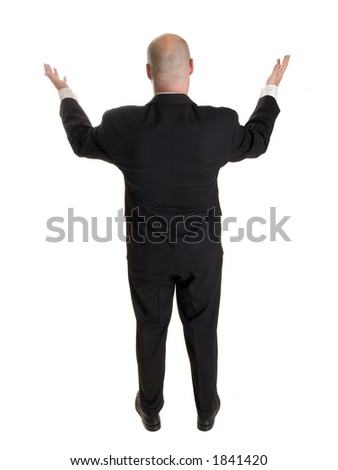 Stock photo of the back side of a well dressed businessman holding his arms up in a gesture as if addressing a crowd or requesting a congregation to rise.