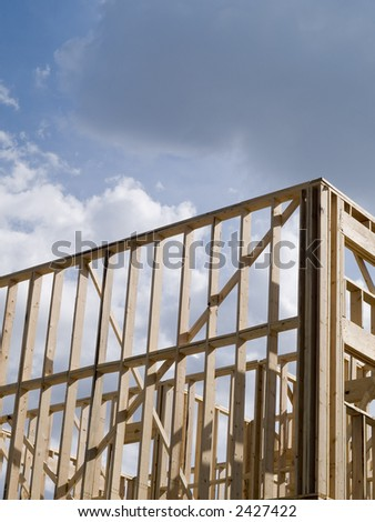 Stock photo of the wood frames of a new urban housing development under construction against a blue sky with white clouds.