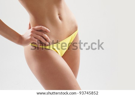Stock photo of young, fit and sexy woman in yellow swimsuit - stock photo
