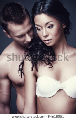 Stock photo of young sensitive couple in sexy pose on dark background - stock photo