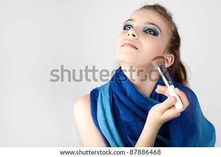 Stock Photo: Portrait of the beautiful woman with make-up brushes near attractive face. - stock photo