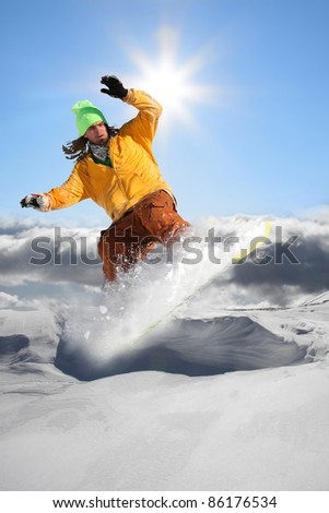 Stock Photo: Snowboarder jumping against blue sky