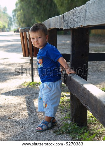stock photo with a boy standing outside in the park