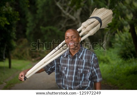 Stock photograph of a smiling black South African entrepreneur small business broom salesman in Hilton, Pietermaritzburg, Kwazulu-Natal - stock photo