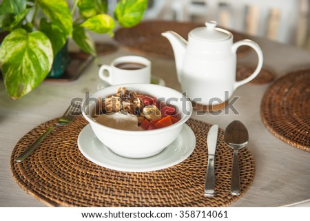 Stock picture of breakfast table with coffee, fruit and yogurt - stock photo