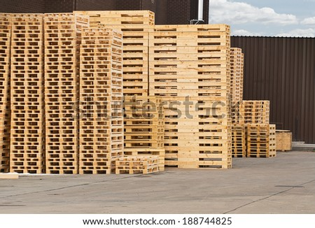Stock Piles of wooden pallets in a yard ready for breaking up and recycling into firewood or kindling - stock photo