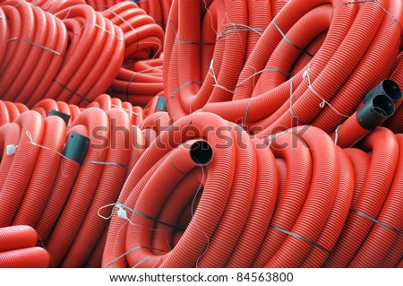 Stock red coiled plastic pipes - stock photo