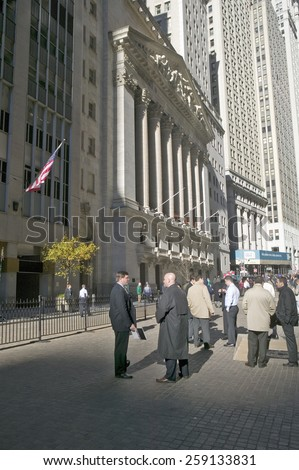 Stock traders take a break in front of the New York Stock Exchange on Wall Street, New York City, New York - stock photo