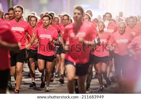 STOCKHOLM - AUG, 16: Closeup of runners in one of the many groups of the Midnight Run (Midnattsloppet) event. Aug 16, 2014 in Stockholm, Sweden - stock photo