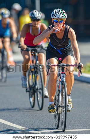 STOCKHOLM - AUG 23, 2015: Female triathlete taking energy drink on the bike at the ITU World Triathlon event in Stockholm. - stock photo