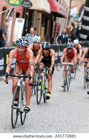 STOCKHOLM - AUG 23, 2014: Kirsten Sweetland (CAN) cycling and leading a group of competitors in the Women's ITU World Triathlon series event August 23, 2014 in Stockholm, Sweden - stock photo